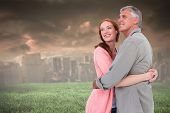 Casual couple hugging and smiling against stormy sky over city