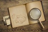 Adventure and travel theme. Diary with magnifying glass or loupe