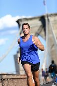 Man runner running on Brooklyn bridge in New York, NYC, USA. Fitness athlete working out after work in afternoon sunset
