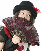 A pretty young teen hiding behind a hand-held fan while dressed fore a Valentine celebration.  On a white background.
