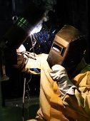 worker-welder mask cooks metallic design on a dark background