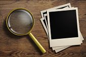 stock photo of polaroid  - magnifying glass or loupe with old polaroid photo frames stack on wood table - JPG