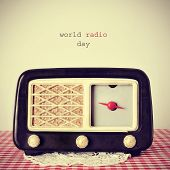 foto of transistor  - the text world radio day and an antique radio receptor on a table covered with a red and white checkered tablecloth - JPG