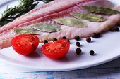 picture of pangasius  - Pangasius fillet with herb and sliced cherry tomatoes on plate and color wooden table background - JPG