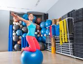 Girl at gym swiss ball knee balance drill exercise workout open arms