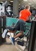 Kneeling leg femoral curl man exercise at gym rear view workout