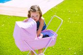 Toddler kid girl playing with baby cart in green turf grass garden