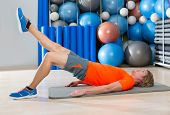 hip lift with leg extension blond man at gym workout with swiss ball background