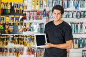 Portrait of smiling young man displaying digital tablet in hardware store