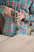 Midsection of carpenter drilling wood at workbench in workshop