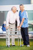 Portrait of smiling caretaker assisting senior man to use walking frame at nursing home lawn