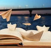 picture of old bridge  - Origami boats on old book on bridge background - JPG