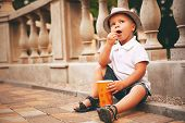 Boy In Hat Sitting Near Balustrade