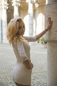 Pretty Blonde Young Woman Against Marble Pillar In European City