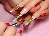 picture of nail-design  - Master draws design floral on female nails.