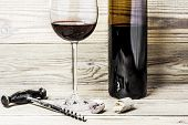 Wine glass, cork, corkscrew and bottle on a wooden background