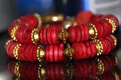 image of bangles  - a traditional red and gold bangle with reflection - JPG