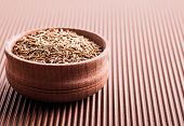 stock photo of cumin  - spice cumin in a wooden bowl on a brown background - JPG