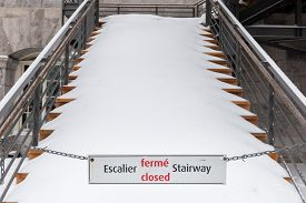 picture of stairway  - Sign of closed stairway in french and English with a stairway in background full of snow - JPG