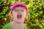 stock photo of laugh out loud  - Little girl standing in a park and shouting loudly - JPG