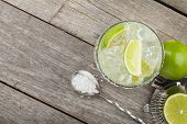 picture of lime  - Classic margarita cocktail with salty rim on wooden table with limes and drink utensils - JPG