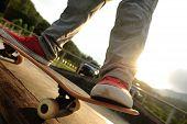 pic of skateboard  - closeup of skateboarder legs skateboarding at sunrise skatepark - JPG