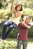 foto of swing  - Teenage Couple Having Fun On Rope Swing - JPG