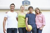 picture of garage  - Portrait Of Teenage Family Playing Basketball Outside Garage - JPG