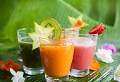 foto of tropical food  - Assortment of fresh  tropical fruits smoothies on the green banana leaves - JPG