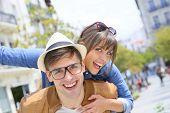 stock photo of piggyback ride  - Man giving piggyback ride to girlfriend in the street - JPG