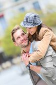 image of piggyback ride  - Young man giving piggyback ride to girlfriend in town - JPG