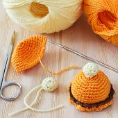 picture of thread-making  - Making of handmade colorful crochet toys sweets with skein on wooden table - JPG