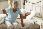 stock photo of senior adult  - Senior Woman Suffering From Backache Getting Out Of Bed - JPG