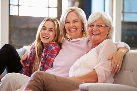 image of grandmother  - Grandmother With Mother And Adult Daughter Relaxing On Sofa - JPG