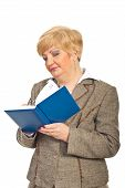 Mature Business Woman Writing In Agenda