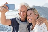 Happy romantic couple embracing on the beach and taking a photo with smart phone. Portrait of senior poster