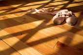 stock photo of pink shoes  - pair of ballet shoes lying on a wooden studio floor - JPG
