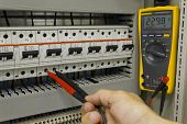 foto of breaker  - Electrical engineer measuring voltage on a miniature circuit breaker - JPG