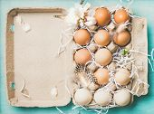Easter Holiday Background. Flat-lay Of Natural Colored Eggs In Box, Tender Almond Blossom Flower And poster