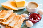 Close Up Table With Delicious Breakfast Coffee, Toasts, Boiled Eggs, Cheese And Strawberry Jam. Cont poster