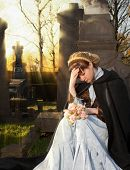 Young Victorian widow mourning on a tombstone at Halloween