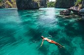 Young woman swimming in clear sea water in lagoon and looking at beautiful landscape. Travelling tou poster