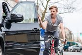 Angry young bicyclist shouting while swerving for avoiding dangerous collision with the open door of poster