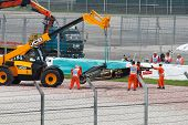 SEPANG, MALAYSIA - APRIL 8: Track officials lifting up Vitaly Petrov's car after he skidded out of t