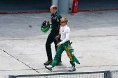 SEPANG, MALAYSIA - APRIL 8:  Heikki Kovalainen of Team Lotus walks back to his pit after a check at