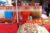 KUCHING, BORNEO ISLAND - MAY 13: Colored fruit extract drinks and barbecued meat on sale in the streets, May 13, 2011 in Kuching, Borneo Island. Street vendors cater to a big number of visitors here.