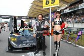 SEPANG - JUNE 19: ThunderAsia's race queen poses with driver Melvin Choo at the start of the Japan SUPER GT Round 3 race in Sepang International Circuit on June 19, 2011 in Sepang, Malaysia.