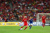 BUKIT JALIL, MALAYSIA - JULY 16: Liverpool's Dirk Kuyt (red) passes as Malaysia's Ismail Fauzi (9) rushes in at the National Stadium on July 16, 2011, Bukit Jalil, Malaysia. Liverpool won 6-3.