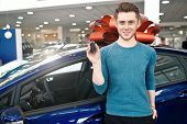 Young Man Is Showing A Key, Looking At Camera And Smiling While Standing Near The Car In Car Dealers poster