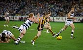 MELBOURNE - SEPTEMBER 9 : Sam Mitchell kicks under pressure from Cameron Ling in Geelong's win over Hawthorn - September 9, 2011 in Melbourne, Australia.